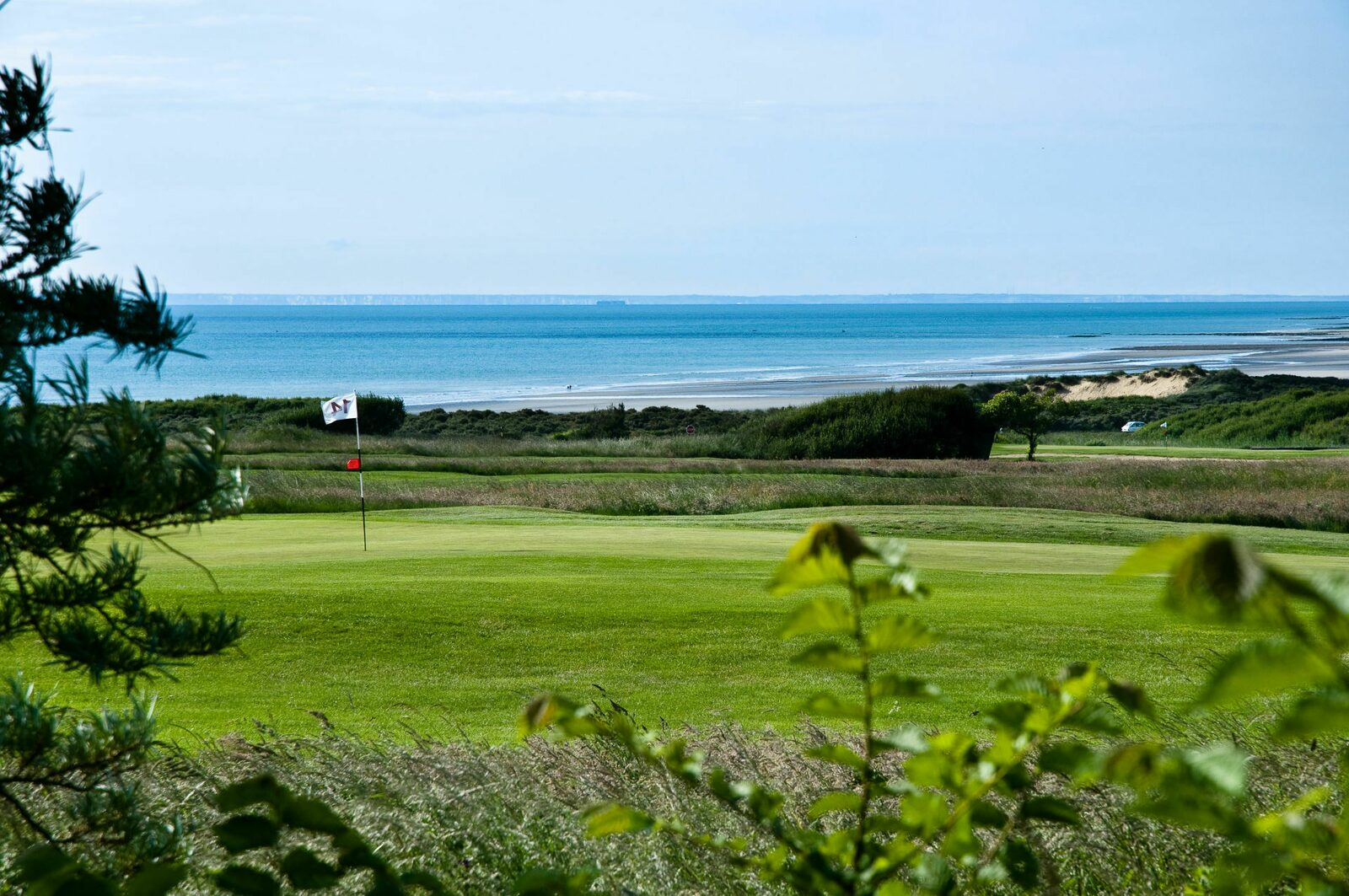 Golf course Golf de Wimereux on a sunny day with the Opal Coast in the background.
