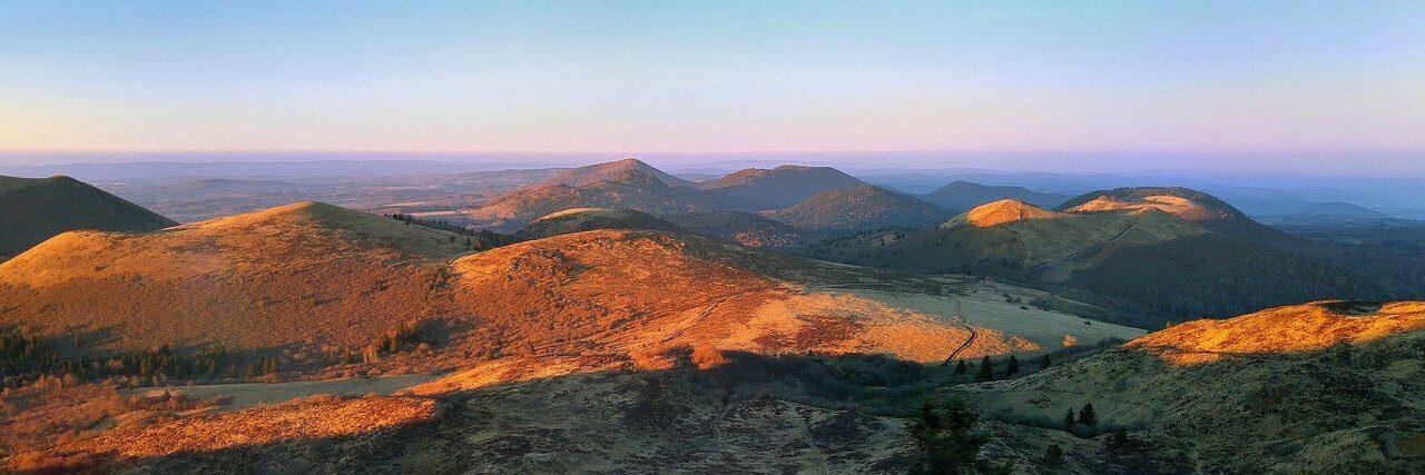 Een foto van het bergachtige landschap in de Auvergne bij zonsondergang.