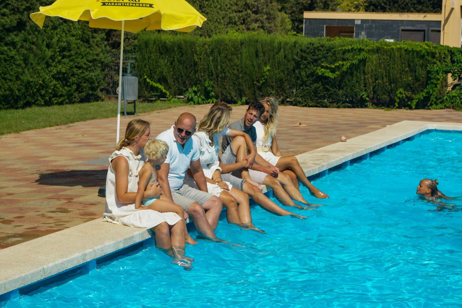 Rand van zwembad gezin
