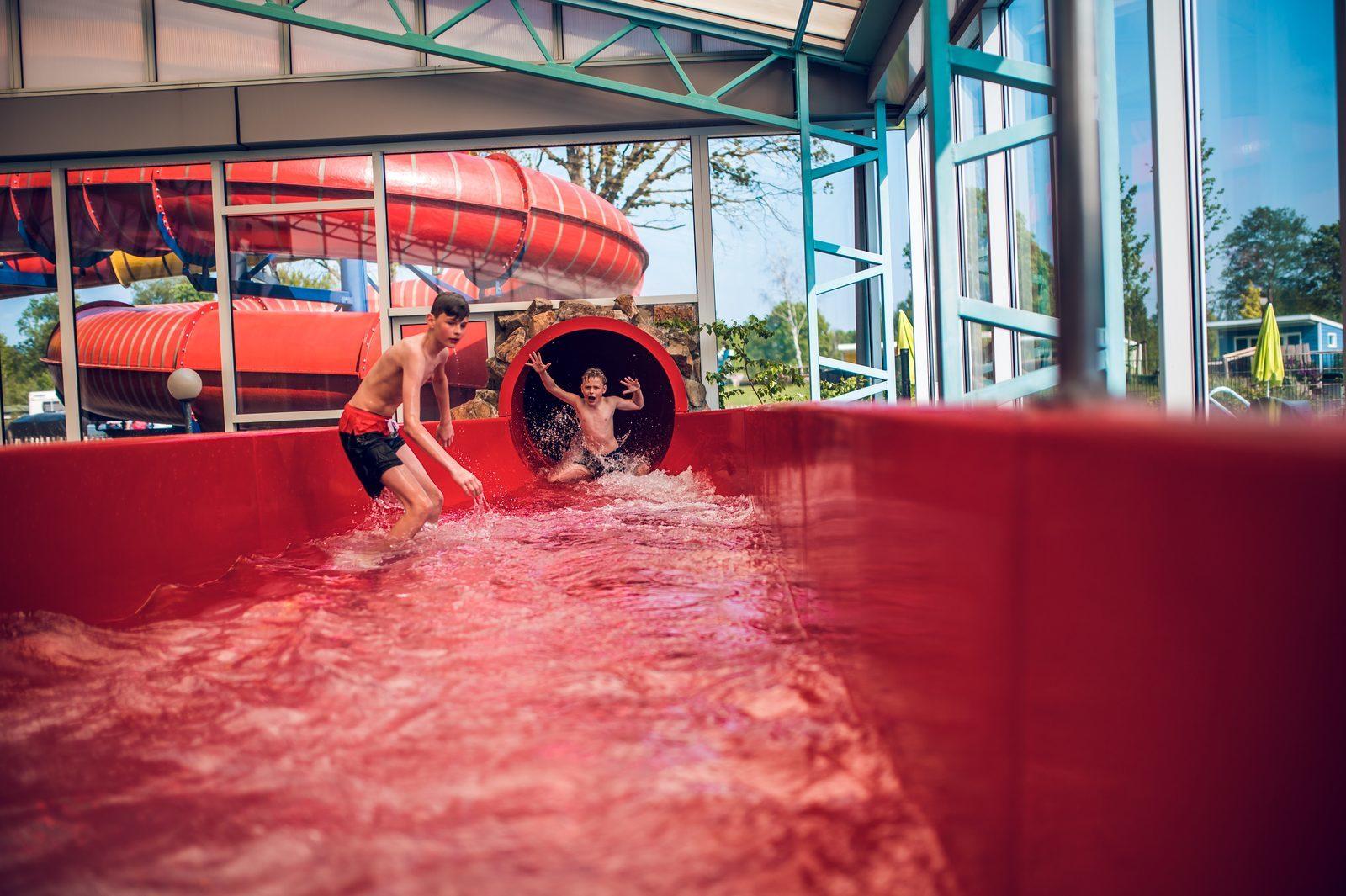 foto jongen uit zwembad glijbaan rood Ackersate